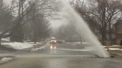 Massive water main break gushing on city street in winter - stock footage