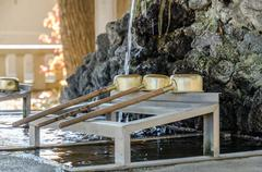 Brass dipper arranged in front of Purification trough in Shinto shrines Stock Photos