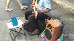 Blind artist playing electric guitar with mini speaker on street for some moeny Stock Footage