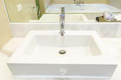 White sink and faucet in a bathroom Stock Photos
