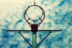 Old neglect basketball backboard with rusty hoop above street court. Blue clo Stock Photos