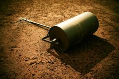 Old rusty iron barrel for maintenance of neglect tennis court. Old dry red cr Stock Photos