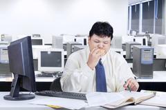 Entrepreneur working while biting burger Stock Photos