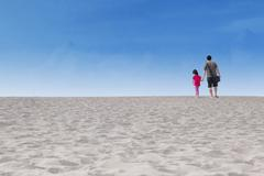 Girl with her father walk on desert Stock Photos