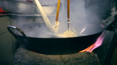 Stock Video Footage of cooking noodles in a cauldron on the street close up