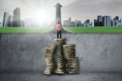 Man standing on books to past the obstacle - stock photo