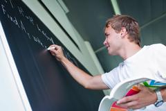 handsome college student solving a math problem during math clas - stock photo