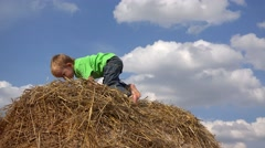 Stock Video Footage of Amusing little child playing on haystack, close blue serene sky, white clouds