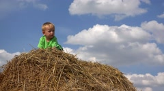Cheeky child climbing on haystack, beautiful summer day, blue sky - stock footage