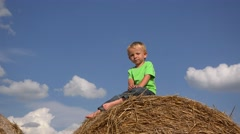 Happy child dancing on haystack close sky, enjoy the summer - stock footage