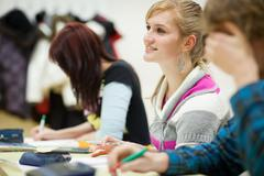 pretty, female college student sitting in a classroom full of st - stock photo