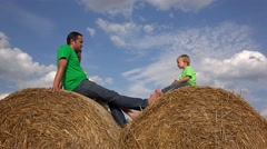 Young parents and little child relaxing on haystack close blue sky Stock Footage