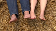 Man and woman bare feet relaxing on haystack, soles touch - stock footage