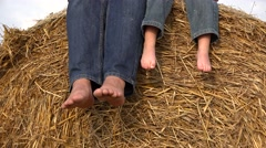 Father and son bare feet relaxing on haystack, soles palying Stock Footage