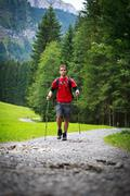 active handsome young man nordic walking/hiking in mountains, en - stock photo