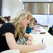 young pretty female college student sitting in a classroom full - stock photo