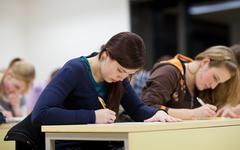 pretty female college student sitting in a classroom full of stu - stock photo