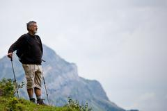 Stock Photo of active handsome senior man nordic walking outdoors on a forest p