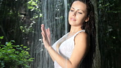Young woman standing under streams of falling water in the forest Stock Footage