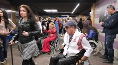 People with disabilities in wheelchairs among a crowd in a public building. Stock Footage