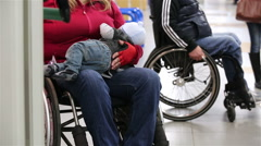 Young woman with a disability in a wheelchair holding a her baby. Stock Footage