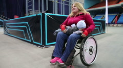 Young woman with a disability in a wheelchair holding a baby. Stock Footage