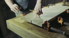 joiner glues two workpiece of wooden plank together - stock footage
