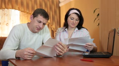 Frustrated young husband and wife who read some bad news in a letter Stock Footage