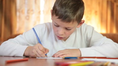 Cute boy drawing or doing homework at the table in living room Stock Footage