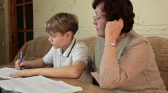 Grandma helping her grandson doing homework sitting at a desk in the living room Stock Footage