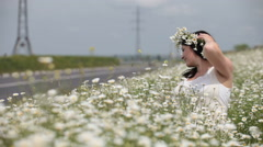 Young pregnant woman with wreath sitting in camomiles on the roadside Stock Footage