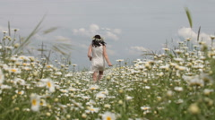Young pregnant woman leaving afar through the chamomile field in summer Stock Footage