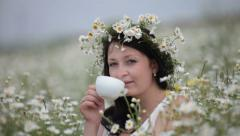 Young woman drinking from a cup sitting among the daisies on the lawn Stock Footage