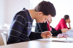 young, handsome male college student sitting in a classroom full - stock photo