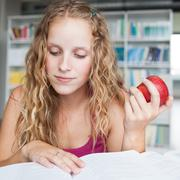 pretty female college student in a library (shallow DOF; color t - stock photo