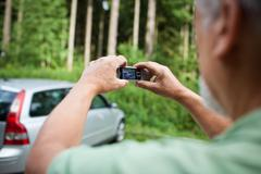 Stock Photo of Insurance company guy taking pics of a newly insured vehicle.