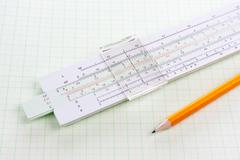Slide rule on squared paper with wooden pencil Stock Photos