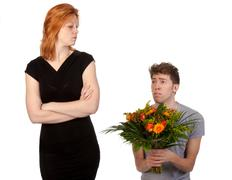 Young boy offering a bunch of flowers to his angry girlfriend - stock photo