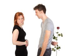Passionate man hidden a rose behind his back for his girlfriend Stock Photos