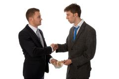 Businessman shaking hands. The deal is made and one businessman is paying the Stock Photos