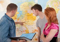 Three colleagues are in a discussion in front of a map of the Neth Stock Photos
