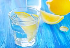 Water with lemons in the glass and on a table Stock Photos