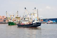 URK, THE NETHERLANDS - MAY 19: Decorated fishing ships are leaving the harbor - stock photo