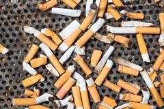 Cigarettes in a big iron ashtray - stock photo