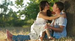 Young couple relaxing on the grass under a tree in the sunshine on a fall day Stock Footage