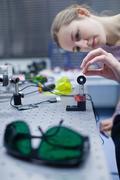 Female scientist doing research in a quantum optics lab (color t Stock Photos