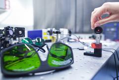 female scientist doing research in a quantum optics lab (color t - stock photo