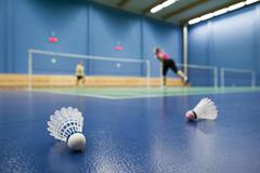 Stock Photo of badminton - badminton courts with players competing; shuttlecock