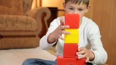 Child playing with colored blocks on floor in the room Stock Footage