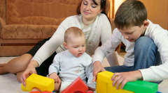 Young mother with children playing colored blocks on the floor of living room Stock Footage